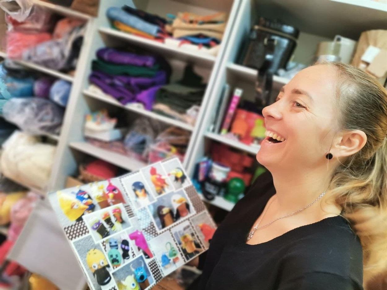 Мария с каталогом шапок из шерсти, которые изготовляет под собственным брендом